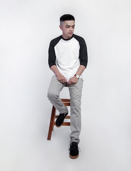 Young handsome man wearing raglan t-shirt is sitting in a chair while posing