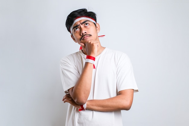 赤と白のヘッドバンドを身に着けている若いハンサムな男は、質問を心配し、心配し、あごに手で緊張していると考えています