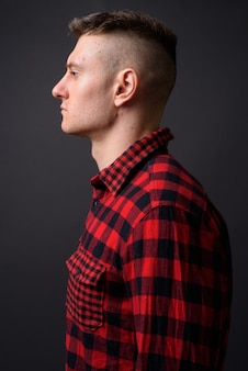 Young handsome man wearing red checkered shirt on gray