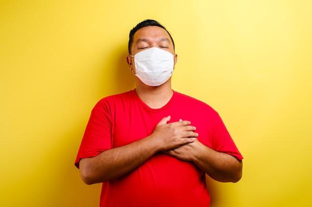 赤いtシャツとサージカルマスクを身に着けている若いハンサムな男は、目を閉じて、顔に感謝のジェスチャーで胸に手を笑顔で孤立した背景の上に立っています。健康の概念。