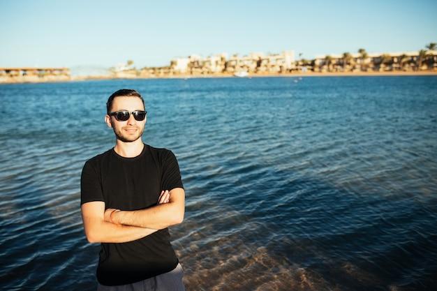 眼鏡をかけて海のビーチで楽しんでいる若いハンサムな男