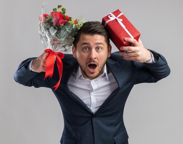 장미 꽃다발과 발렌타인 데이 선물을 들고 양복을 입고 젊은 잘 생긴 남자는 흰색 벽 위에 서 혼란과 놀란