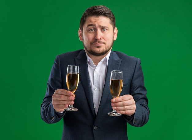 Young handsome man wearing suit holding glasses of champagne going to celebrate valentine's day alone   going to cry with sad expression on face