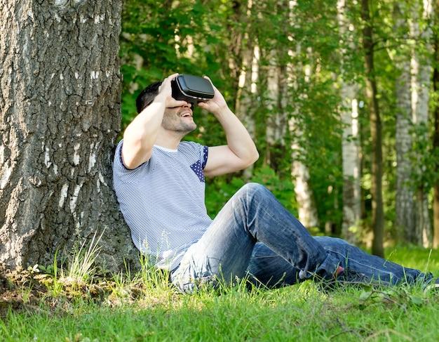 都市公園でバーチャルリアリティヘッドセットを身に着けている若いハンサムな男
