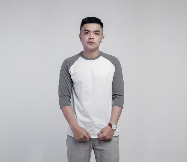 Young handsome man wearing white grey raglan t shirt isolated on space