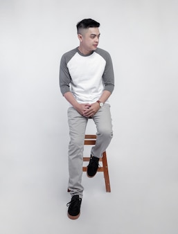 Young handsome man wearing white grey raglan t shirt was sitting in chair