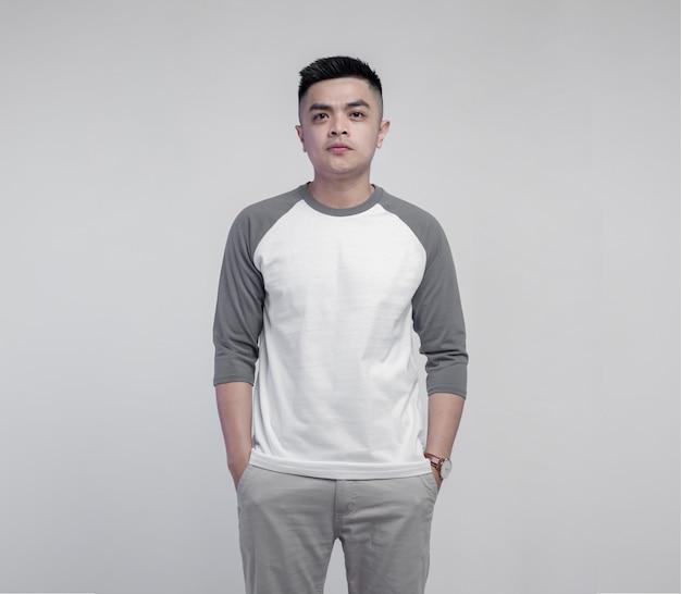 Young handsome man wearing white grey raglan t shirt