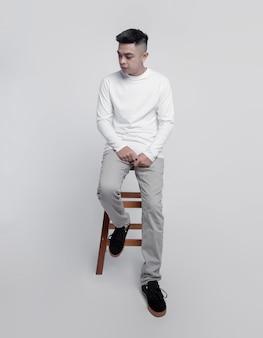 白い長袖tシャツを着ている若いハンサムな男は椅子に座っています。
