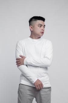 Молодой красавец в белой футболке с длинным рукавом, изолированной на простом фоне