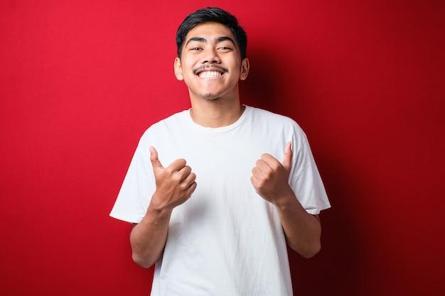 赤い背景の上に白いtシャツを着ている若いハンサムな男は、手で前向きなジェスチャーをすることを承認し、笑顔で成功を喜んで親指を立てます。勝者のジェスチャー。