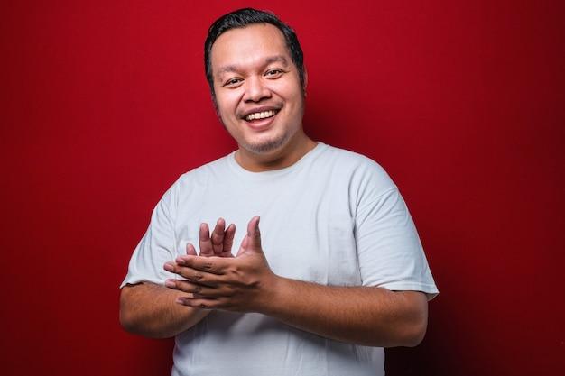 赤い背景の上に白いtシャツを着て、幸せで楽しい拍手と拍手、誇らしげな手を一緒に笑って若いハンサムな男