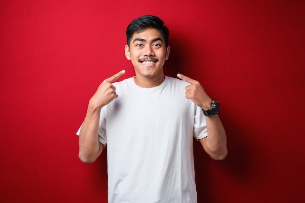 Молодой красавец в белой футболке, стоящий на изолированном красном фоне, улыбаясь, веселый показывая и указывая пальцами, зубами и ртом. концепция стоматологического здоровья.