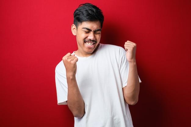孤立した赤い背景の上に立っている白いtシャツを着た若いハンサムな男は非常に幸せで興奮して腕を上げ、笑顔で成功のために叫んで勝者のジェスチャーをしています。お祝いのコンセプト