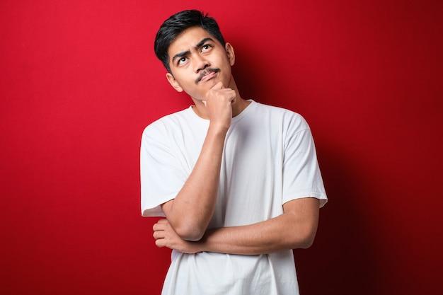 赤い背景の上に立っている白いtシャツを着ている若いハンサムな男質問を心配して考えて、心配し、あごに手で緊張