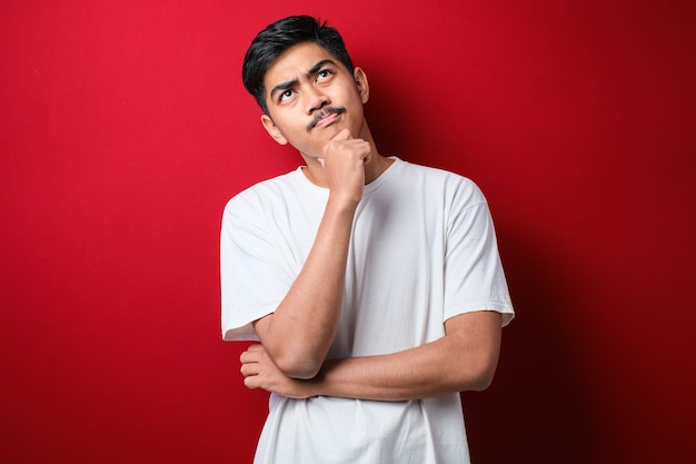 Young handsome man wearing white t-shirt standing over red background thinking worried about a question, concerned and nervous with hand on chin