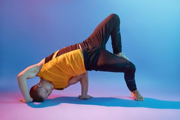 黄色のtシャツと体のバランスのためのヨガの練習をしている黒のズボンを着ている若いハンサムな男