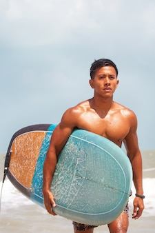 若いハンサムな男が体全体に濡れて、ビーチの上を歩いて手にサーフィンボードを保持