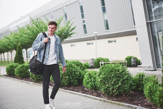 空港に急いで彼の肩にバッグを持つ若いハンサムな男。