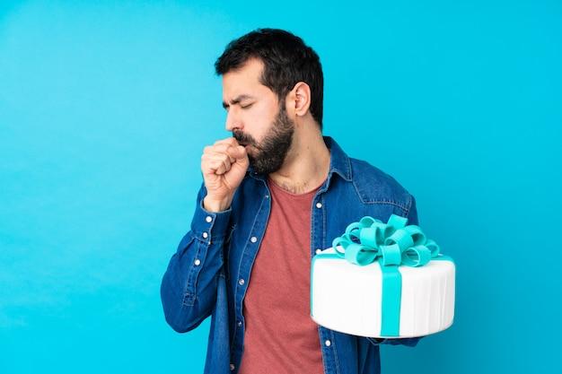 Молодой красивый мужчина с большим тортом над синей стеной страдает от кашля и плохо себя чувствует