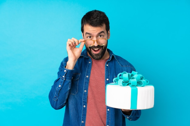 Молодой красавец с большой торт над синей стеной в очках и удивлен