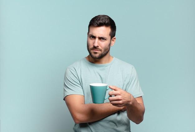 コーヒーカップを持つ若いハンサムな男。朝食のコンセプト