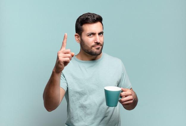 コーヒーカップを持った若いハンサムな男。朝食のコンセプト
