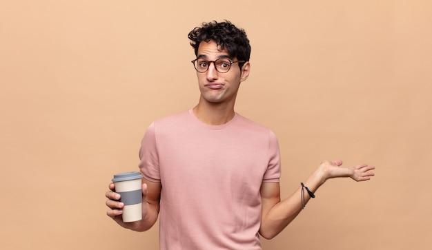 戸惑い、混乱し、疑って、重みを付けたり、面白い表現でさまざまなオプションを選択したりするコーヒーの若いハンサムな男
