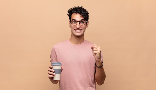 コーヒーを飲んでいる若いハンサムな男は、ショックを受け、興奮し、幸せになり、笑い、成功を祝い、すごい!