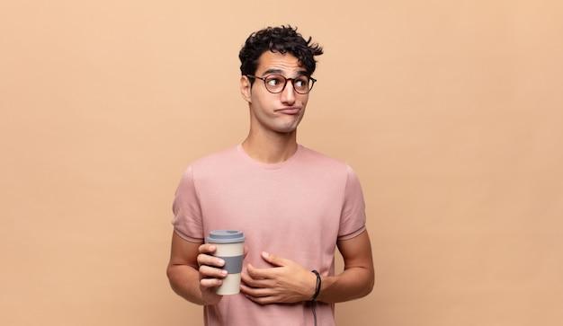 コーヒーを肩をすくめる、混乱して不確かな感じ、腕を組んで困惑した表情で疑う若いハンサムな男