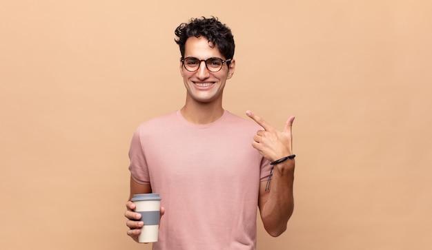 자신의 넓은 미소, 긍정적이고 편안하고 만족스러운 태도를 자신있게 가리키며 웃고 있는 커피를 가진 젊고 잘생긴 남자