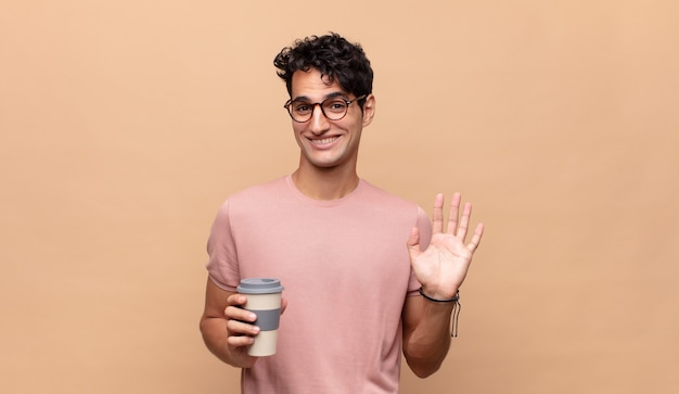 幸せにそして元気に笑って、手を振って、あなたを歓迎して挨拶するか、さようならを言うコーヒーを持った若いハンサムな男