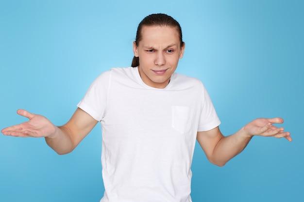 青い背景に分離されたtシャツで彼の顔に疑いを持つ若いハンサムな男。