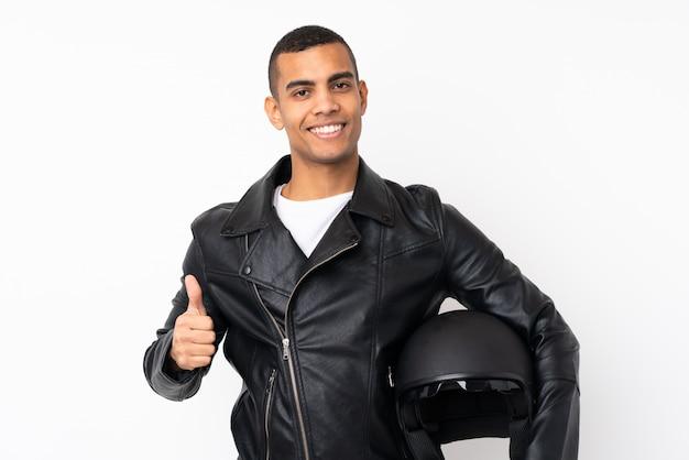 親指ジェスチャーを与える分離の白い壁にオートバイのヘルメットを持つ若いハンサムな男