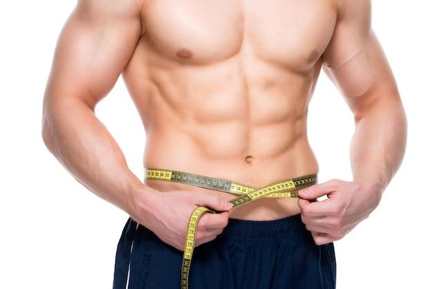 근육질 몸통을 가진 젊은 잘 생긴 남자는 흰 벽에 절연 측정 테이프를 사용합니다.