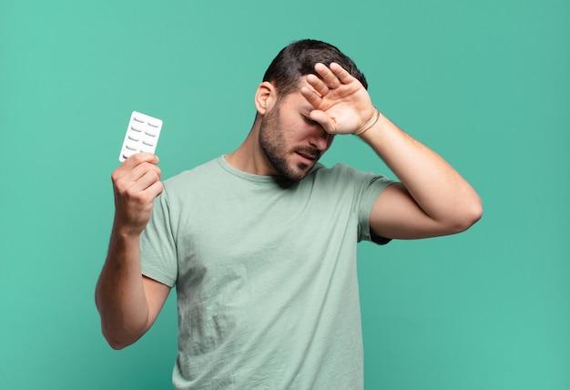 錠剤の錠剤を持つ若いハンサムな男。病気や痛みの概念