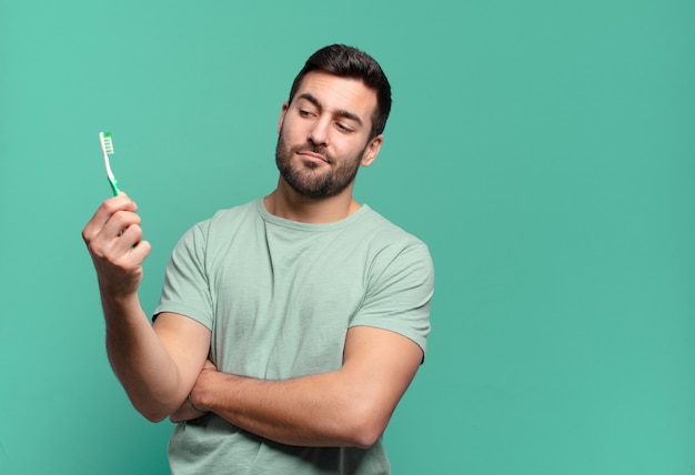 歯ブラシを持つ若いハンサムな男。