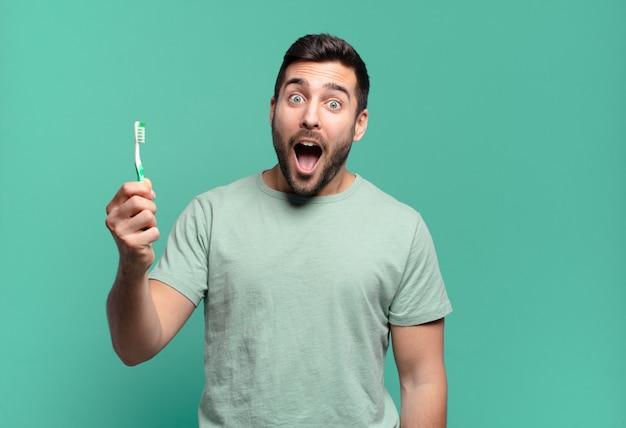 歯ブラシを持つ若いハンサムな男