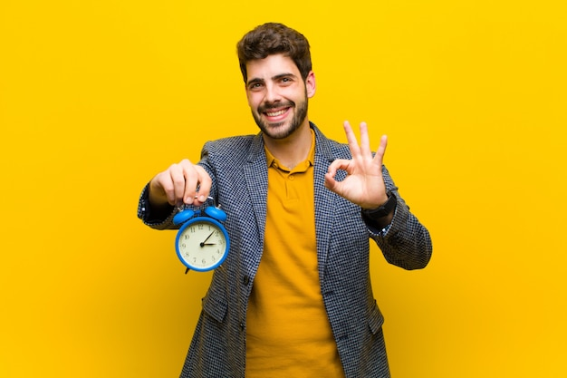 Young handsome man with an alarm clock against orange background