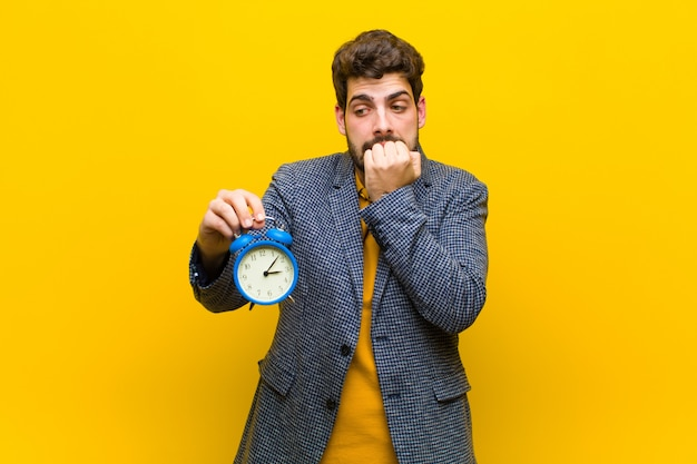 Young handsome man with an alarm clock against orange wall