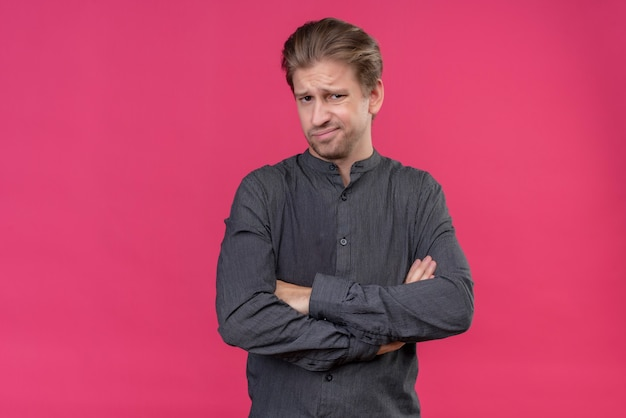 Giovane uomo bello con le braccia incrociate con espressione disgustata in piedi sopra il muro rosa