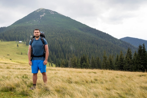 Young handsome man with backpack standing in mountain grassy valley on copy space background of summer woody mountain peak and blue sky.