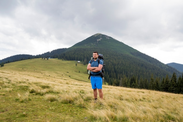 Young handsome man with backpack standing in mountain grassy valley