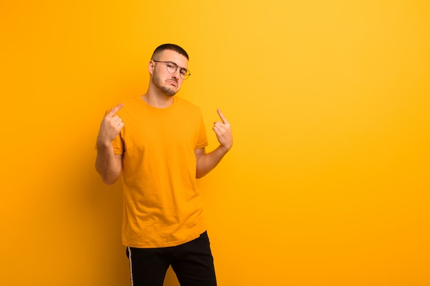 Young handsome man with a bad attitude looking proud and aggressive, pointing upwards or making fun sign with hands against flat background