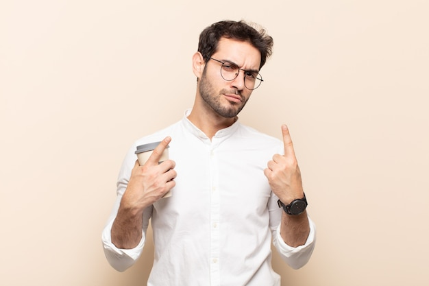 Young handsome man with a bad attitude looking proud and aggressive, pointing upwards or making fun sign with hands