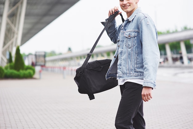 Young handsome man with a bag on his shoulder in a hurry to the airport.