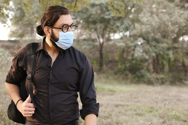 Young handsome man with a bag on his shoulder and wearing protective mask