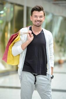 買い物袋を持つ若いハンサムな男。