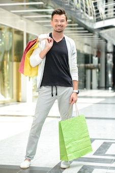 Young handsome man with bags for shopping.