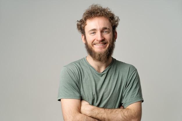 Молодой красавец с бородой и вьющимися волосами в оливковой футболке, глядя в камеру изолированы