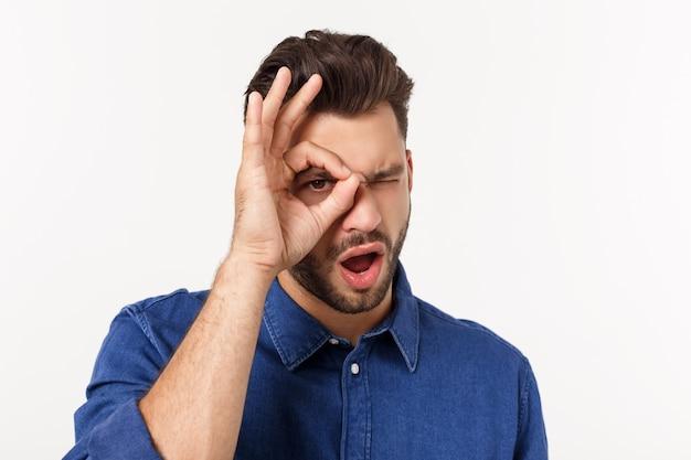 Okのしぐさをしているひげと若いハンサムな男は驚いた顔、指で見ているとショックを受けた。信じられない表現。